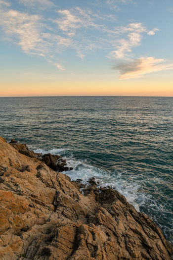 sunset on the rocks Rocks And Sea Sea Sunset Tranquility Serenity Natural Beauty Relaxing In Nature Sea Beach Sunset Horizon Over Water Landscape Nature Scenics Sky Water Beauty In Nature Tourism Outdoors Sunlight Backgrounds Vacations Wave Travel Destinations