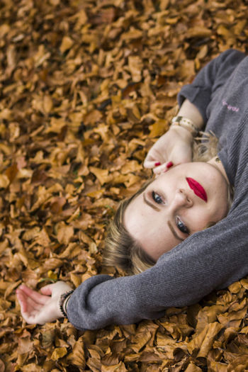 High angle portrait of woman lying down on autumn leaves