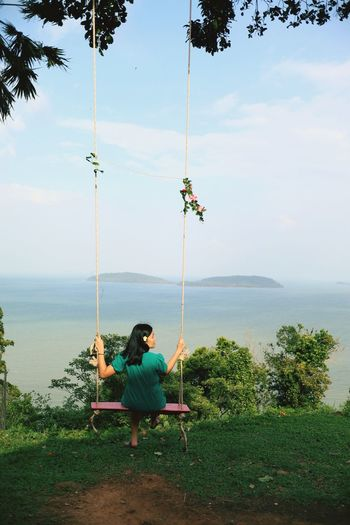 Man sitting on swing in sea against sky