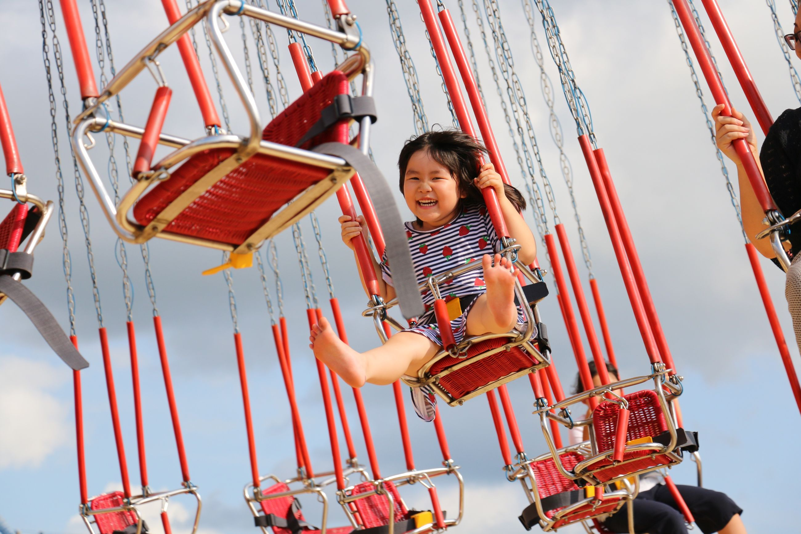 childhood, enjoyment, fun, smiling, leisure activity, elementary age, real people, happiness, low angle view, amusement park, one person, full length, front view, looking at camera, lifestyles, day, excitement, playing, cheerful, jumping, amusement park ride, girls, outdoors, portrait, carousel, young adult, people