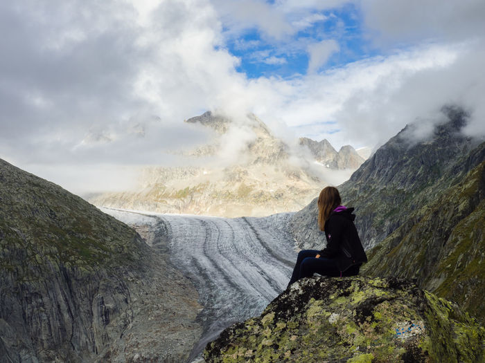Woman Sitting On Rock Against Cloudy Sky