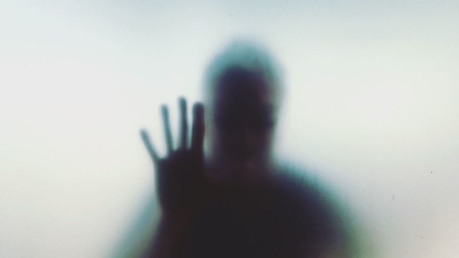Shadow of person hand on glass