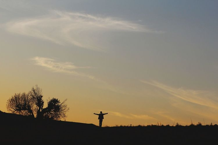 Silhouette man with arms outstretched standing on field against sky at sunset