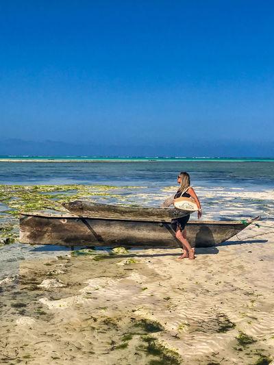 Woman walking by abandoned boat at beach
