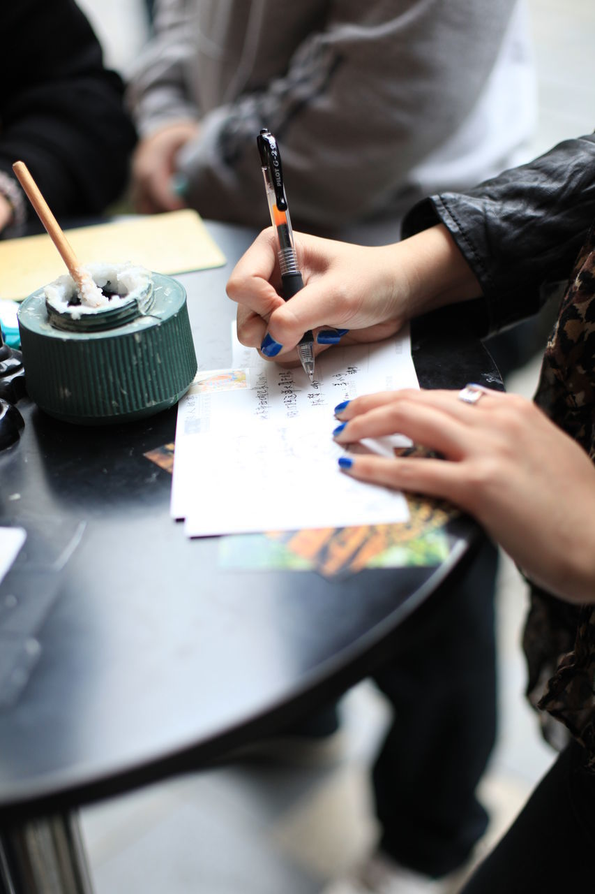High Angle View Of Woman Hand Writing On Paper At Table
