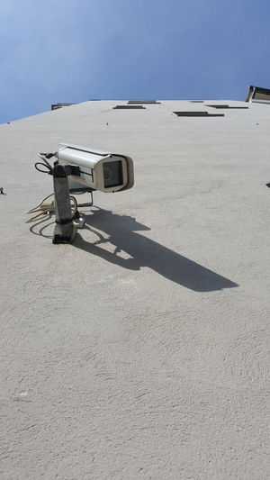 Security cam on a wall in a sunny day