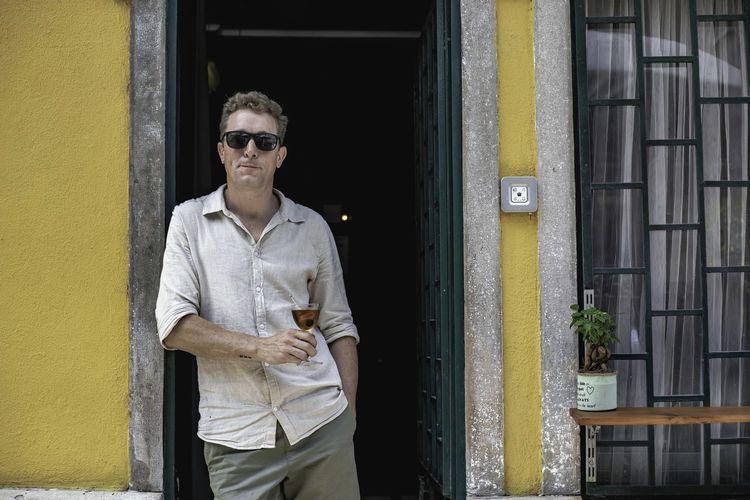 Portrait of young man standing against yellow door