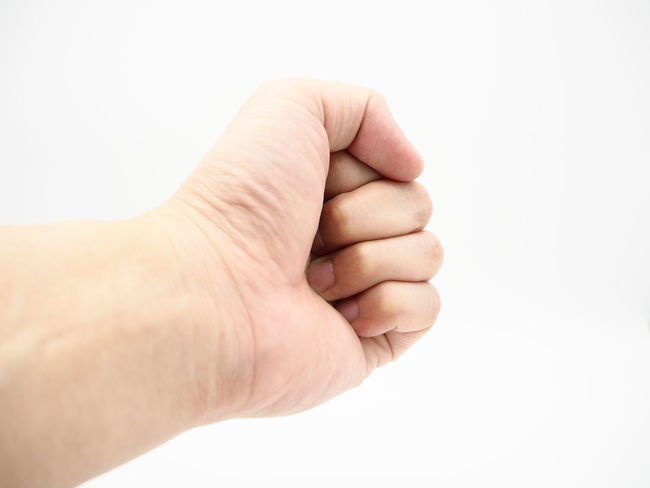 Man clenched fist isolated on a white background. Adult Body Part Close-up Contemplation Copy Space Cut Out Finger Fist Gesturing Hand Holding Human Arm Human Body Part Human Finger Human Hand Human Limb Indoors  Men People Studio Shot Teenager Thumb White Background