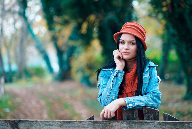 Portrait of beautiful young woman standing against trees