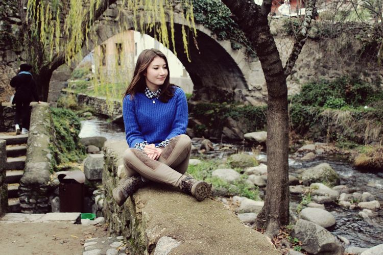 Woman Sitting On Retaining Wall Against Arch Bridge