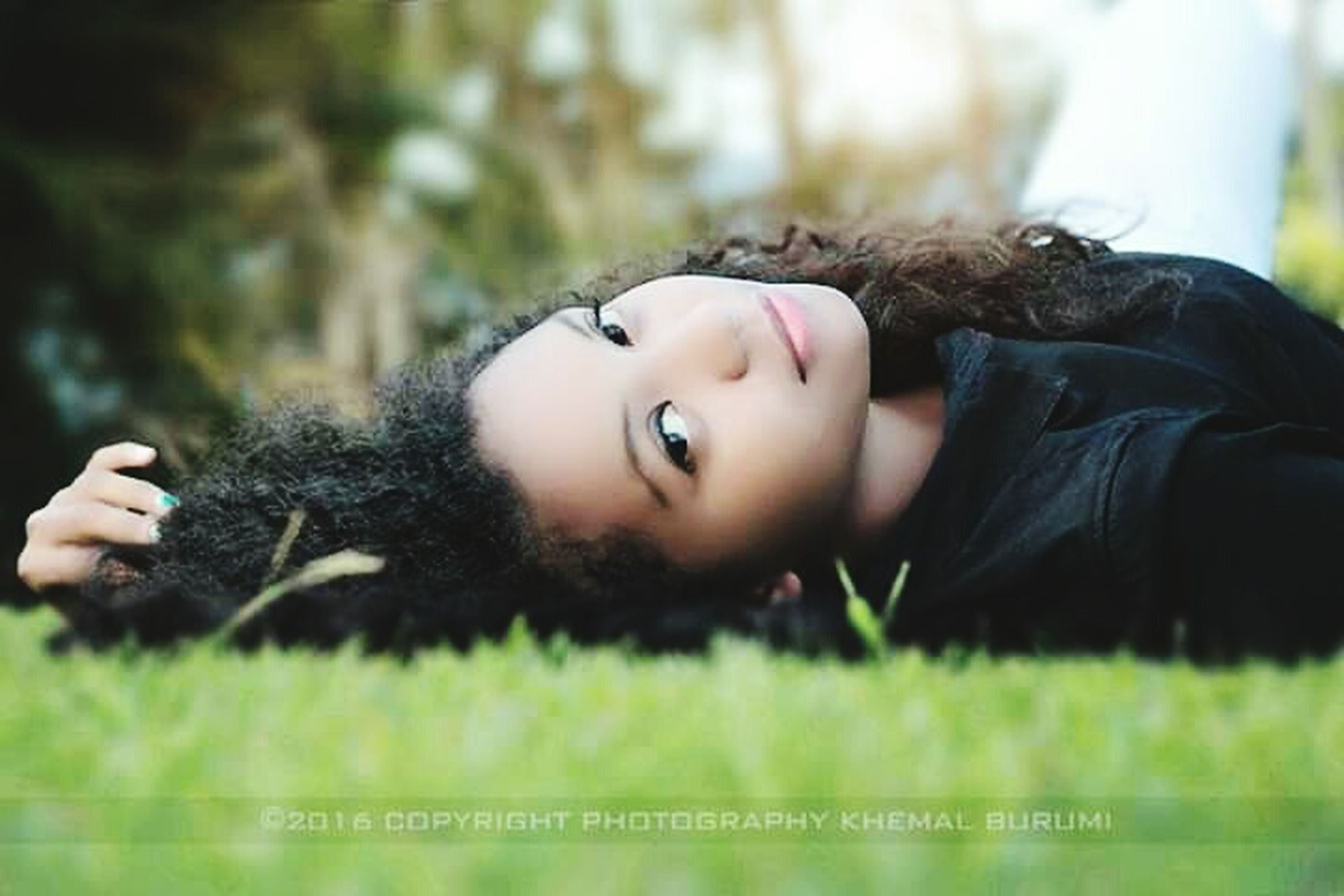 one person, lying down, portrait, child, childhood, looking at camera, plant, relaxation, nature, day, brown hair, offspring, grass, headshot, tree, casual clothing, hair, hairstyle, contemplation, innocence, beautiful woman