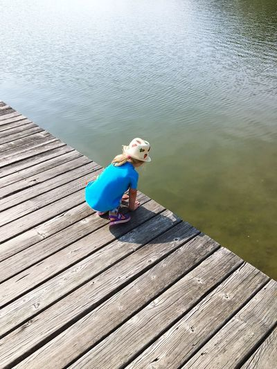 Girl with hat and blue shirt at a lake Water Surface Wood Lake Summer Girl Childhood Child Water One Person Real People Lifestyles Full Length High Angle View Leisure Activity Nature Outdoors