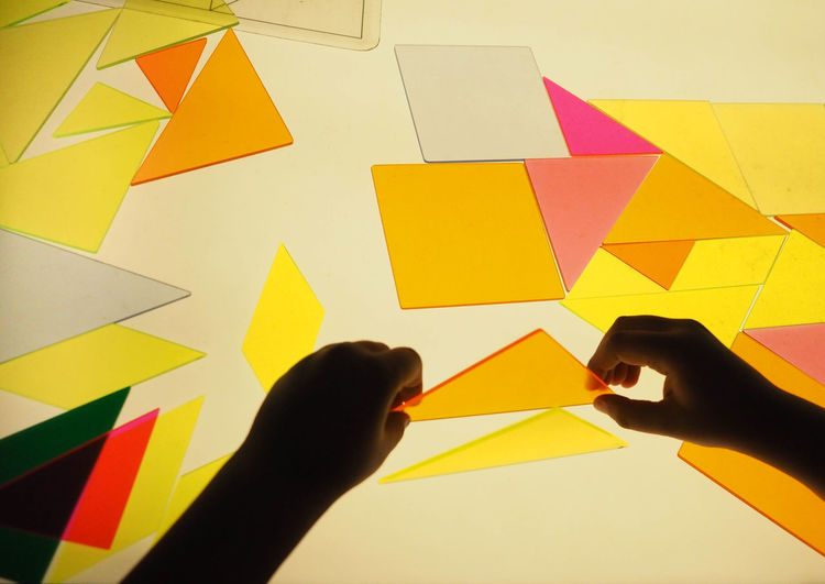 Human Hand Hand Human Body Part Real People Body Part Finger Human Finger Indoors  Personal Perspective Multi Colored Unrecognizable Person Lifestyles One Person Leisure Activity Yellow Paper Creativity Shape Holding Human Limb Playing Play Tangram  Light And Shadow Light