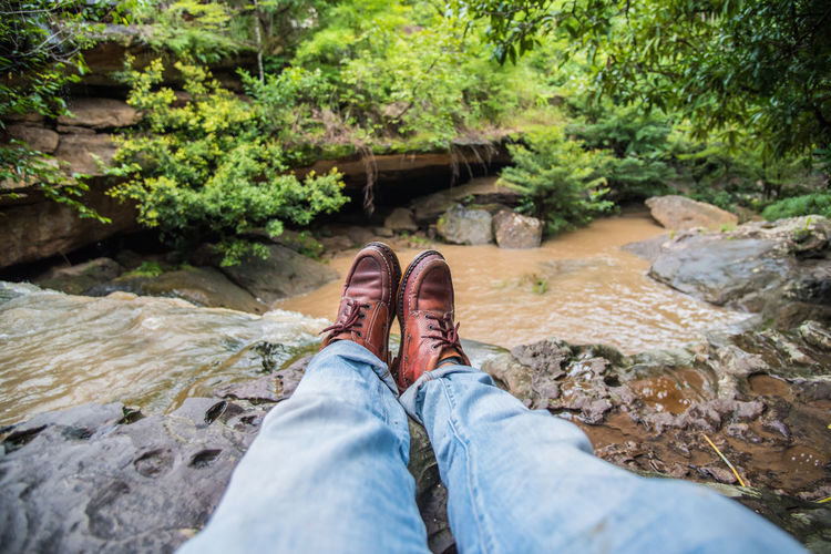 Low section of man relaxing against stream at forest