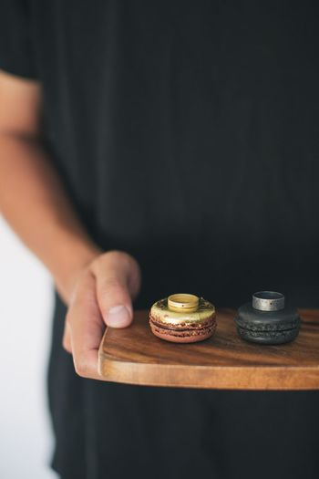 Midsection of man holding macaroons with ring on tray while standing indoors