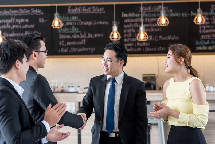 Business Businessman Cheerful Colleague Communication Cooperation Corporate Business Day Formalwear Friendship Greeting Group Of People Indoors  Meeting Men Occupation Real People Smiling Suit Teamwork Togetherness Well-dressed Women Working Young Adult