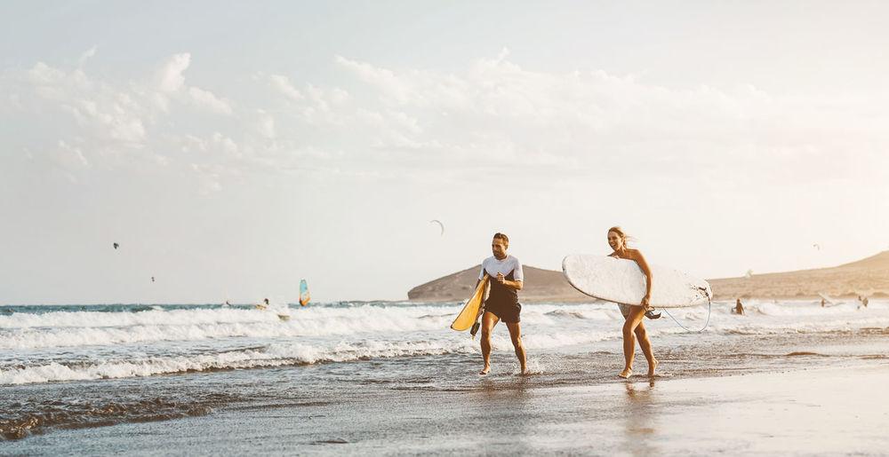 Couple holding surfboard walking on beach against sky