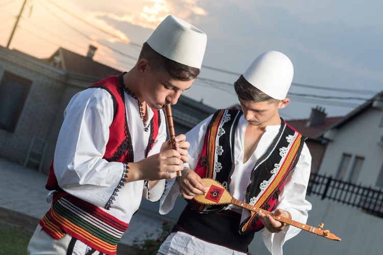 teen boys in traditional albanian costume playing music with flute and string instrument in the evening sunlight Albania Albanian Kosovo Traditional Culture Traditional Clothing Flute Flute Player Holding Kosova Musical Instrument Musician Outdoors People Playing String Instrument Teen Two People