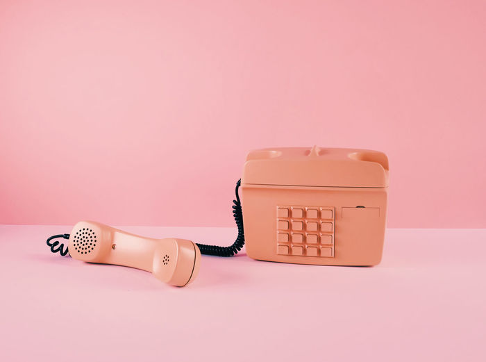 Close-up of telephone booth on table against pink background