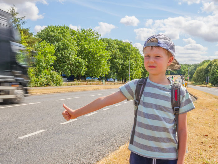 Day view little child boy traveller with backpack catching car on UK road Casual Clothing Child Childhood Day Front View Gesturing Hitchhiking Human Arm Innocence Leisure Activity Lifestyles Looking At Camera Nature One Person Outdoors Real People Road Standing Transportation Tree