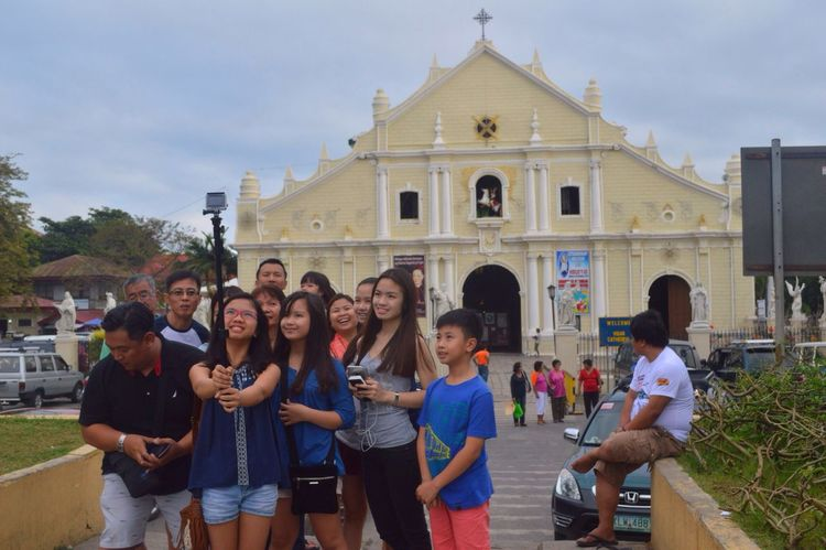 A family who spends their vacation together, stopping-by and takes a groufie. Behind them is the Vigan City's St. Paul Cathedral. Vigancity Vigan Philippines Vacation Photography Streetphotography