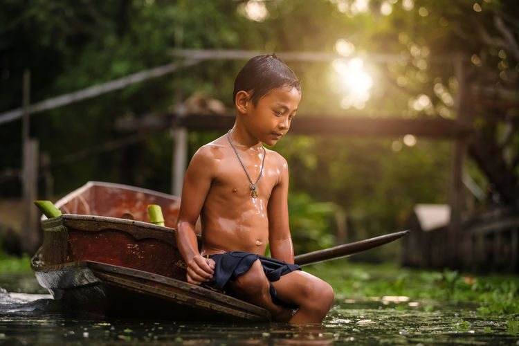 Portrait of shirtless wet boy on boat in river