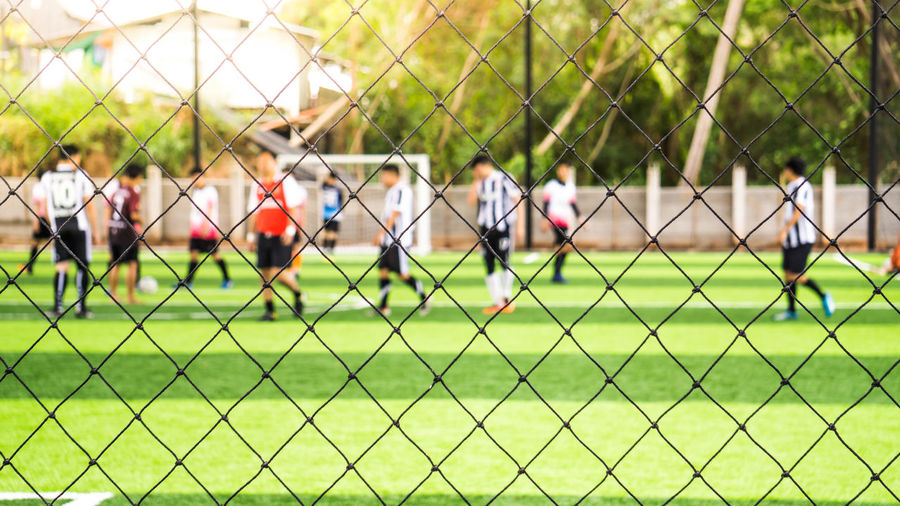 Men playing soccer on field seen through chainlink fence