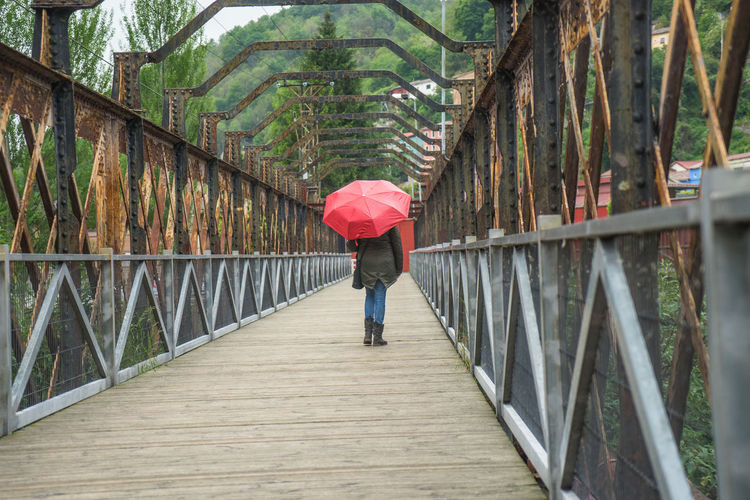 Rear View Of Woman With Umbrella Walking On Covered Bridge