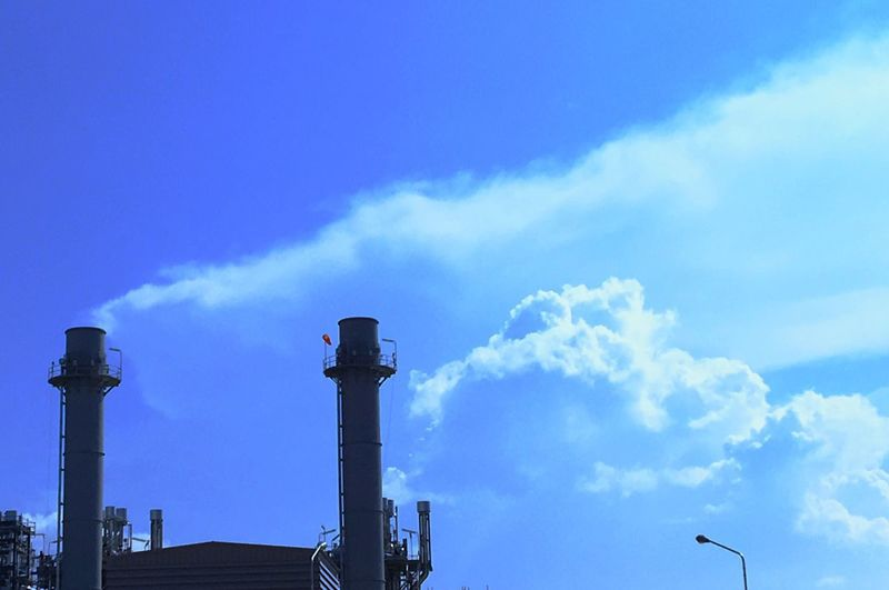 Clouds look like where The Smoke Of The Chimney Industry Sky Factory Cloud - Sky Chimney Built Structure Day Emitting Low Angle View Blue No People Outdoors Fumes Architecture Building Exterior