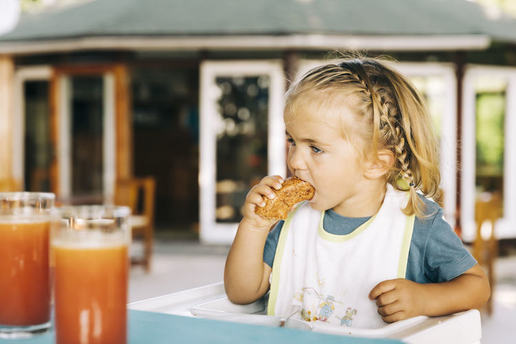 Portrait of cute boy eating food at restaurant