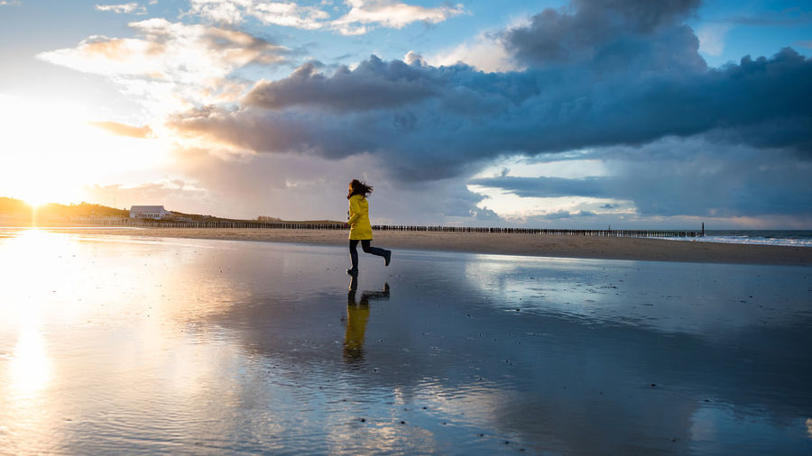 Woman Running On Shore At Beach Against Sky