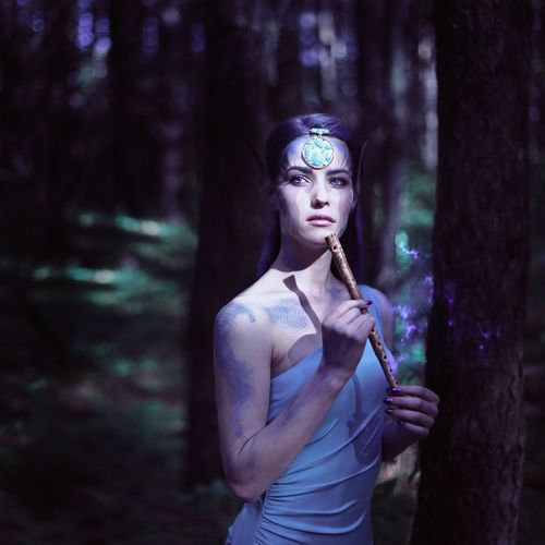 Thoughtful young woman looking away while standing by tree trunk in forest