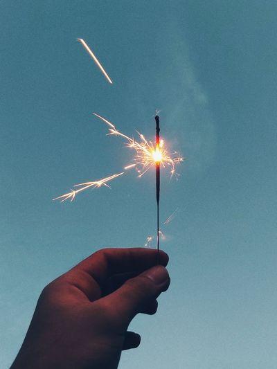 Hand holding sparkler against sky