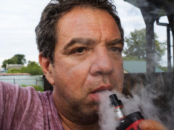 Close-Up Portrait Of Man Smoking Electronic Cigarette