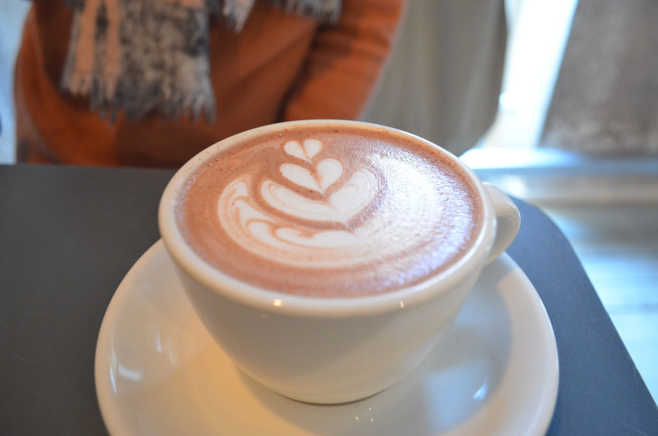 coffee cup, coffee - drink, refreshment, drink, cappuccino, food and drink, frothy drink, saucer, froth art, table, latte, focus on foreground, indoors, close-up, freshness, day, no people