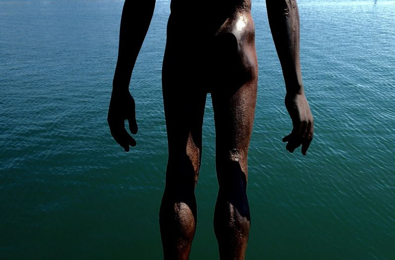 Midsection of naked man standing by sea