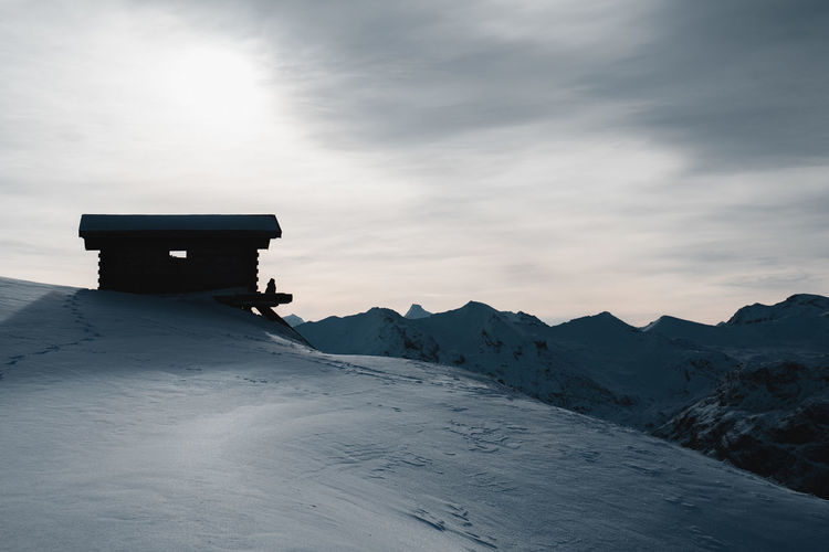 Lifeguard hut on snowcapped mountain against sky