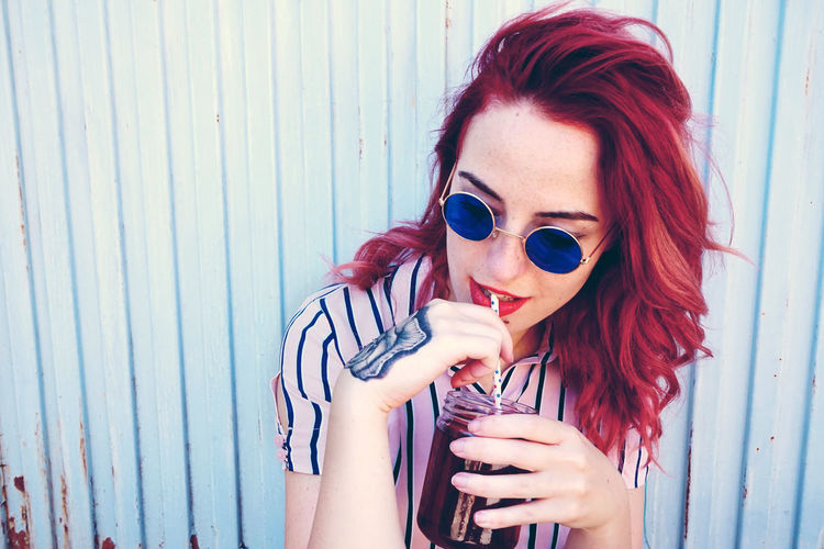 Beverage Adult Beautiful Woman Casual Clothing Day Drink Drinking Glass Dyed Hair Fashion Front View Glasses Hair Hairstyle Holding Leisure Activity Lifestyles One Person Outdoors Portrait Real People Redhead Sunglasses Women Young Adult Young Women