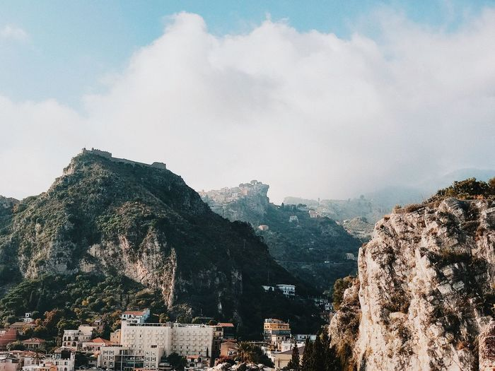 Panoramic view of townscape by mountain against sky