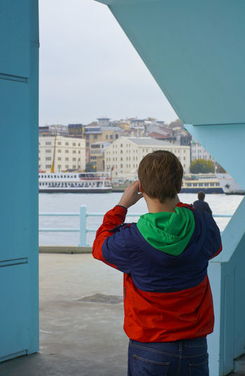Rear view of boy standing against sky in city