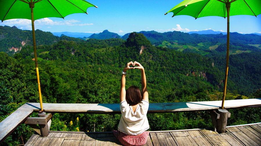 Woman making heart shape on footbridge against blue sky