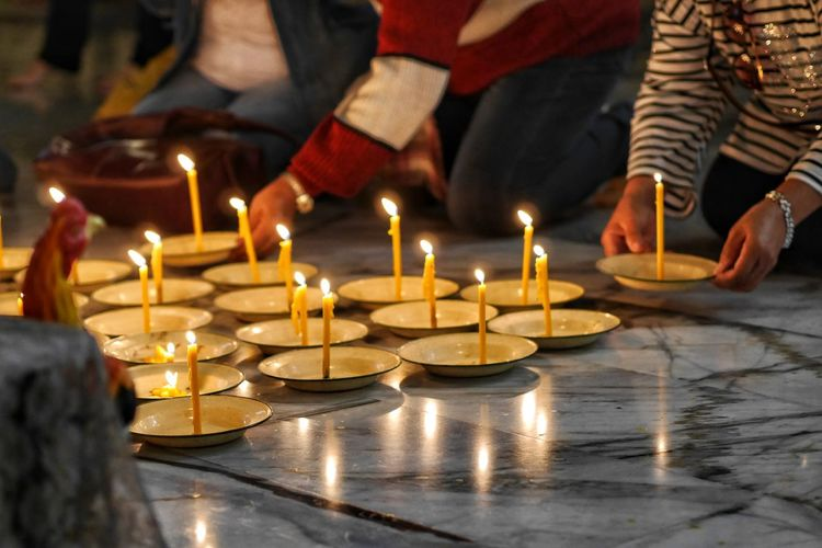 Midsection of people with illuminated candles on tiled floor in church