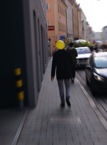 A man walking along the street with a yellow balloon Paint The Town Yellow Architecture Balloon Head Balloons🎈 Blurred Motion City Day One Person Outdoors People Real People Rear View