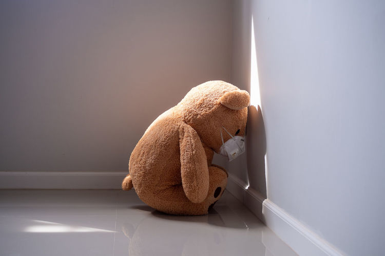 Close-up of stuffed toy bear with protective face mask kneeling on gray wall at home