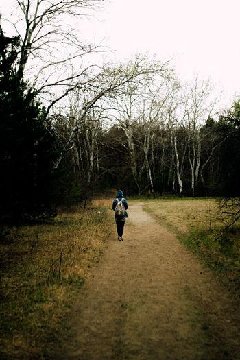 Rear view of man walking on dirt road