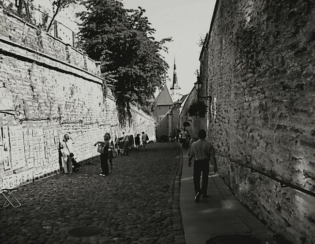 Tallinn Estonia B&w Cobblestone Streets Oldworld Brick Barrier People Walking  Tourism Stepbackintime
