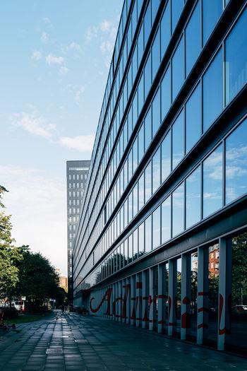 Street by modern buildings against sky in city