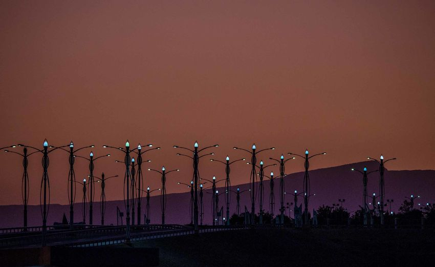 Silhouette people against illuminated street lights against orange sky