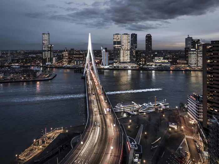 High angle view of illuminated bridge over river by buildings against sky