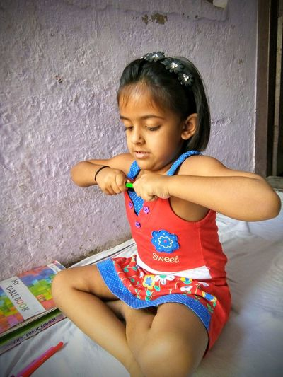 Little girl opening pencil cap Books 5-7 Years Portrait Power Asian  Sweet Cute Babygirl Homework Education Home Girl Kid Indian Indian Culture  Young Girl Window Light Pencil Pen Difficult Force Forcefully Childhood Child Full Length Sitting Girls Casual Clothing One Baby Girl Only Little